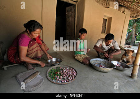BANGLADESH Alpona Ritchil of the Garo tribal minority prepares vegetables for cooking while her husband Farid and son Homar clean the fish for their meal, Haluaghat, Mymensingh region photo by Sean Sprague - Stock Image