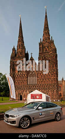 Lichfield Cathedral with banners ready for the 2013 Lichfield Festival with BMW car in foreground. BMW sponsor the - Stock Image