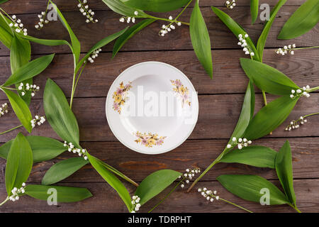 Plate and decor of lily of the valley flowers on the background of vintage wooden boards. Vintage background with flowers and place under the text. Vi - Stock Image