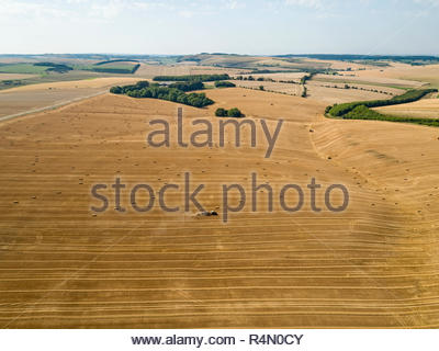 Aerial landscape of tractor baler straw bales in farm fields after wheat harvest in summer - Stock Image