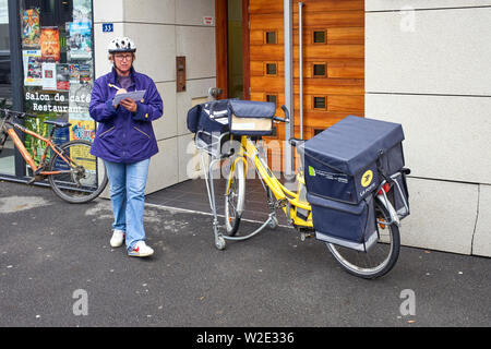 French postwoman and electric delivery bike - Stock Image
