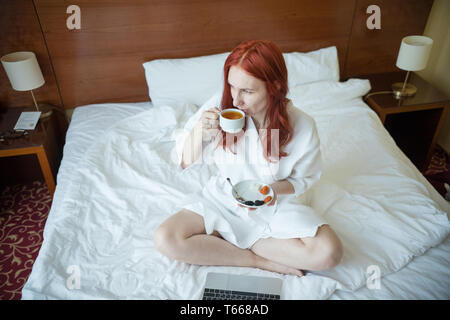 A ginger woman sitting on the bed in the hotel room and drinking tea - Stock Image