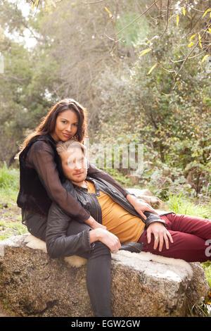 Man lying on woman's lap on rock. - Stock Image