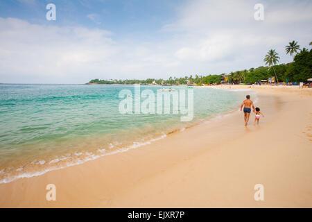 FATHER AND DAUGHTER WALKING ON UNAWATUNA BEACH - Stock Image