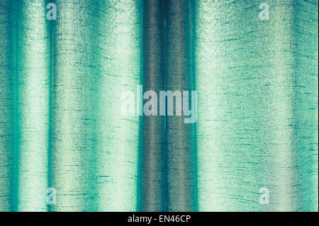 Part of a drawn pair of green curtains made from synthetic material - Stock Image