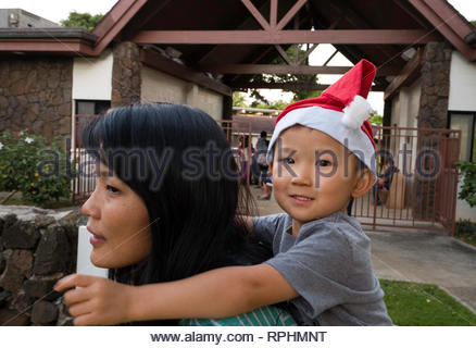Young boy wearing a Santa hat stocking cap getting a piggyback ride from a woman, Kahala, Honolulu, Oahu, Hawaii, USA - Stock Image