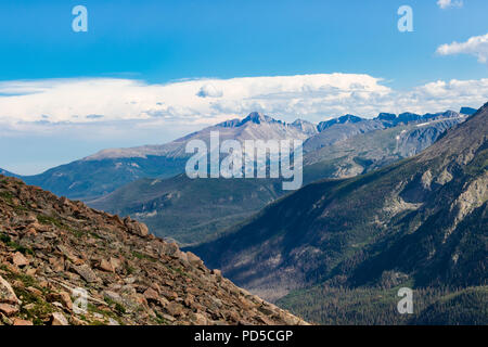 Sunny Colorado Rockies, with rocky hill in  left-front, dramatic  blue-grey mountains behind, with evergreens below. Bright blue sky  and clouds above - Stock Image