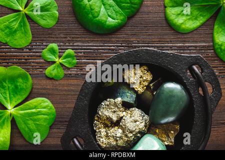 Pot of Pyrite, Green Aventurine, Jade and Peridot with Shamrocks on Dark Wood - Stock Image
