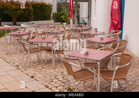Empty tables outside a hotel in Portugal. - Stock Image