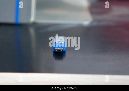 A blue memory stick or usb flash drive with copy space on a desk - Stock Image