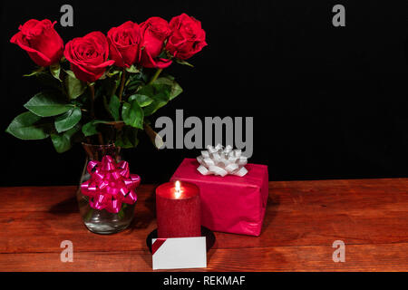 Beautiful red roses in vase with pink bow wrapped present and red candle with name tag on wooden table on dark background. Valentines, Mothers Day, Ea - Stock Image