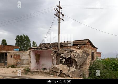 Telephone pole through a derelict building Albania - Stock Image