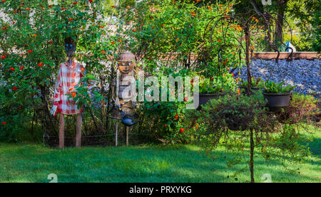 JONESBOROUGH, TN, USA-9/29/18: Two scarecrows, depicting homeowner gardeners, made from baskets and wood sticks stand in a flower-filled yard. - Stock Image
