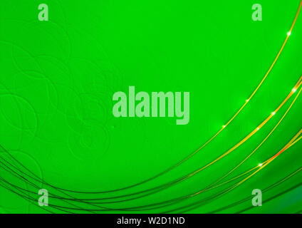Bright light green background with scabrous texture and convex circles and covered thin curved Golden intersecting stripes  with highlights - Stock Image