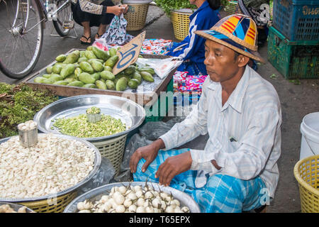 Mae Sot, Thailand - February 3rd 2019: Man in hat selling vegetables on the morning market. The market is open every day. - Stock Image
