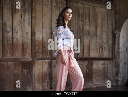 Natural brunette woman posing in front of the wooden gate - Stock Image