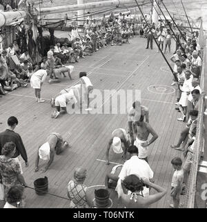 1950s, passenger deck game aboard a Union-castle steamship. Blindfolded passengers have to pick up potatoes that are placed in specific places on the deck. - Stock Image