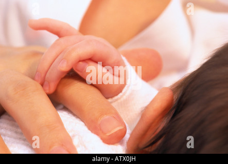 infant's hand resting on mother's hand - Stock Image