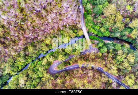 Mountain Galstone road with multiple sharp turns crossing deep creek with running stream over bridge in Berowra creek - part of Greater Sydney. Aerial - Stock Image