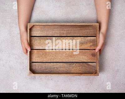 Female hands hold an empty wooden tray. view from above. copy space - Stock Image