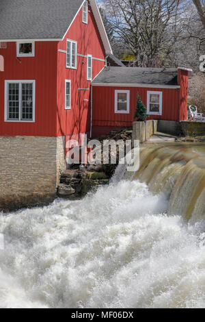 Old red building next to raging waterfall. - Stock Image