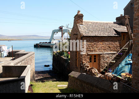 A slipway next to a traditional waterfront house and a catamaran gantry barge in the harbour, Stromness, Orkney. - Stock Image
