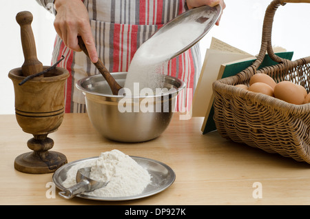 Woman baking a cake, adding the sugar to a bowl & surrounded by the other ingredients. - Stock Image