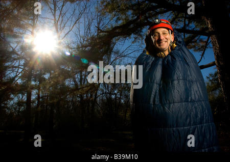 An outdoors enthusiast standing in a sleeping bag in the woods near Fayetteville, Arkansas, U.S.A. - Stock Image