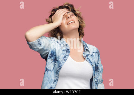 Portrait of sad worried young woman with curly hairstyle in casual blue shirt standing, holding hand on forehead and sad because lost everything. indo - Stock Image