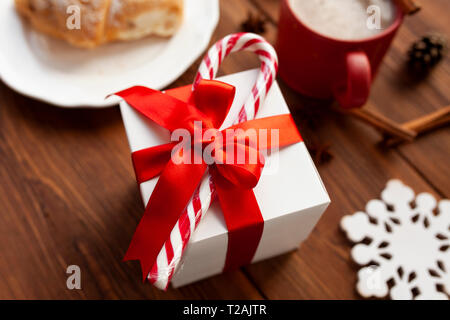 Christmas present with red ribbon and candy cane - Stock Image