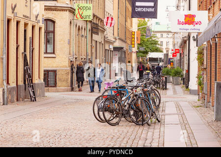 14 September 2018: Gothenburg, Sweden - A typical shopping street, with boutiques, and people walking, and a row of bikes. - Stock Image