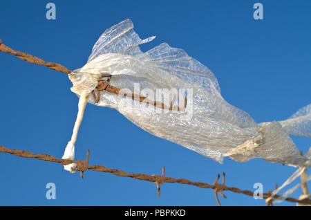 Plastic Waste Litter Pollution  Caught on Rusty Barbed Wire fence - Stock Image