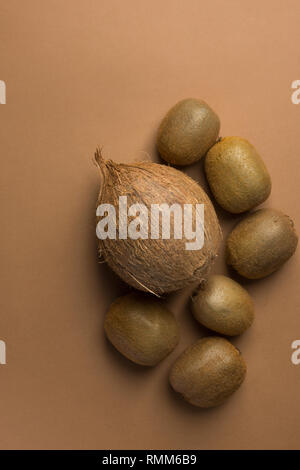 Bunch of ripe organic kiwi coconut on monochrome brown background. Creative flat lay food poster. Vegan vitamins summer tropical fruits. Copy space - Stock Image
