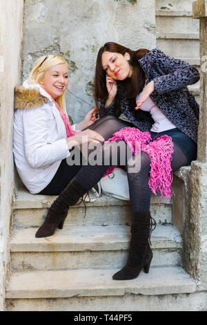 Two teen girls listen to smartphone music sitting outside on staircase smiling using portable headphones - Stock Image