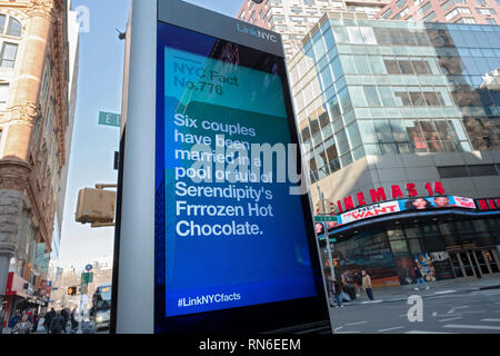 A message on a LINK NYC screen with the fun fact about couples marrying in a pool or tub of Serendipity's Frozen Hot Chocolate. In Manhattan, NYC. - Stock Image