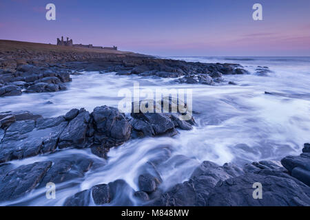 Dunstanburgh Castle at dawn, Craster, Northumberland, England. Spring (March) 2015. - Stock Image
