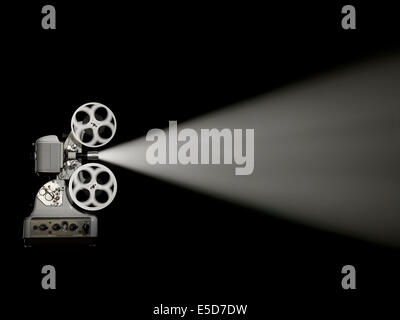 A side shot of an old style film projector on a black background - Stock Image