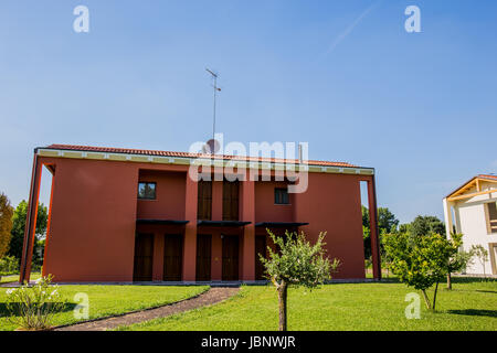A beautiful newly built house with green, big garden in a sunny day - Stock Image
