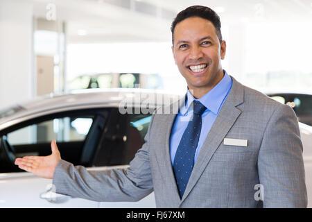 friendly car salesman welcoming gesture at car dealership - Stock Image