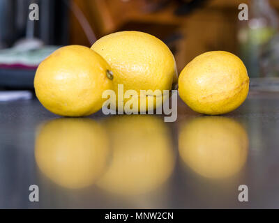 Three Yellow Lemons: Three imperfect lemons reflected on a kitchen counter. - Stock Image