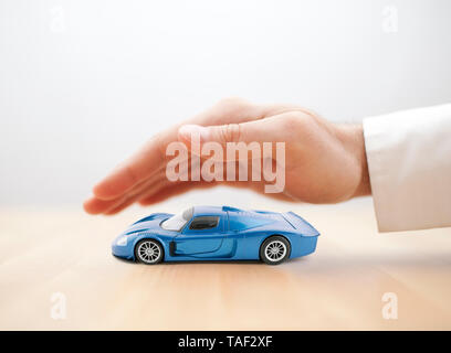 Car insurance concept with blue car toy covered by hand - Stock Image