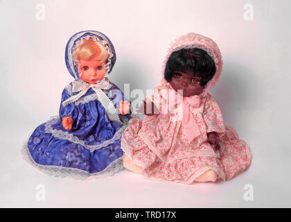 Black and white childrens toy doll wearing pretty dolls clothes sat together white studio background concept ideas image racial harmony & diversity - Stock Image