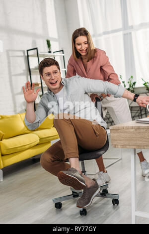 cheerful woman smiling while pushing chair of scared boyfriend - Stock Image