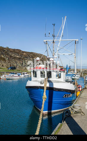 Amlwch Harbour on the north coast of Anglesey with a trawler boat moored up. - Stock Image