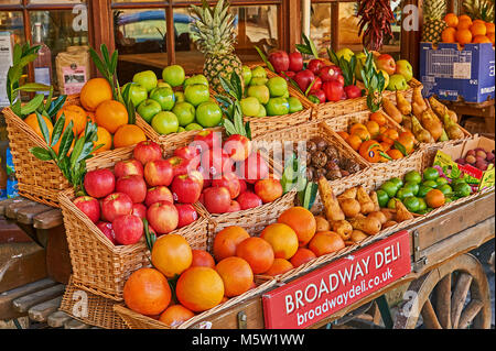 Old fashioned fruit and veg barrow displaying a wide range of fresh fruit and vegetables outside the local deli - Stock Image