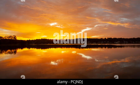 A tranquil orange glow stratus cloudy sunrise  seascape over sea water with water reflections. Queensland, Australia. - Stock Image