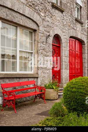 Ireland, Co Leitrim, Drumsna, red painted house beside old stone bridge across River Shannon - Stock Image