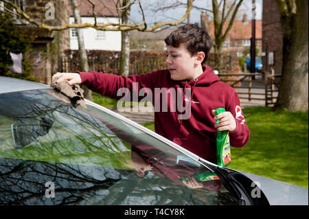Teenage boy cleaning parents car. - Stock Image
