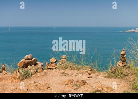 Stack of stones on Promthep cape with Andaman sea on background, Phuket, Thailand - Stock Image