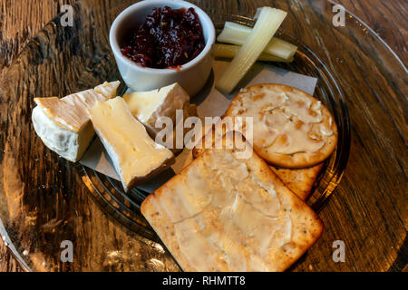 Camembert Cheese buttered biscuits celery and pickle served on a glass plate - Stock Image